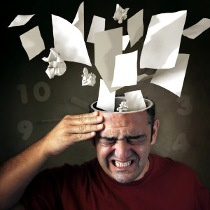 Conceptual image of papers coming out of a mans head with pain expression