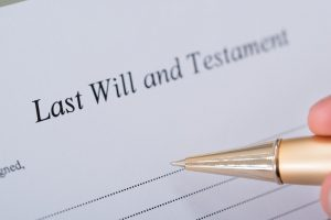 Cropped image of hand signing Last Will and Testament document
