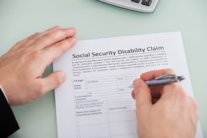 stockfresh_6779024_person-hand-over-social-security-disability-claim-form_sizeS-300x200