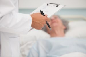 stockfresh_2734888_doctor-holding-clipboard-with-elderly-lady-lying-in-hospital-bed_sizeS_edd5e4-300x200