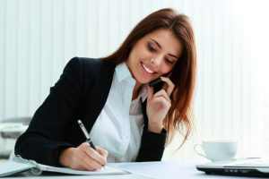 stockfresh_5252485_young-happy-businesswoman-talking-on-the-phone-and-writing-notes-in-office_sizeS-300x200