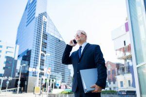 stockfresh_8590344_senior-businessman-calling-on-smartphone-in-city_sizeS-300x200